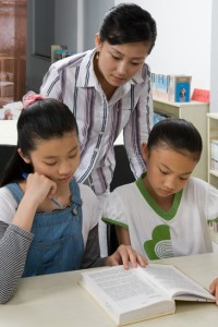 A teacher helping students with their reading